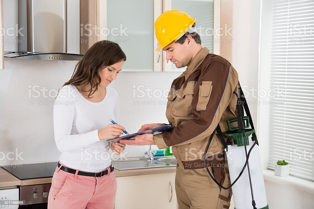 Woman Signing Document In Front Of Exterminator stock photo