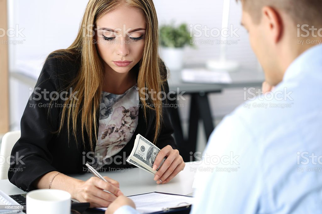 Woman signing documents after reseiving a batch of handred dolla stock photo