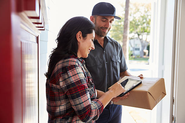 Woman Signing For Package From Courier At Home stock photo