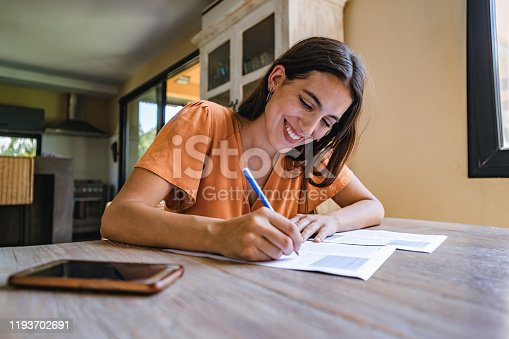 Beautiful Latino woman is sitting at a desk and signing papers.
