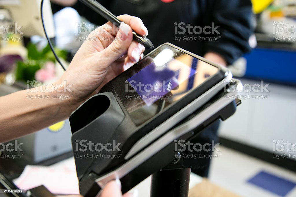 Woman signing payment terminal stock photo