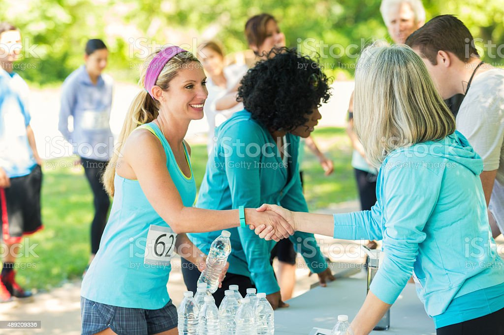 Woman signing up for 5k or marathon race in park stock photo