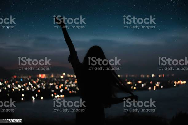 Photo of woman silhouete touching the stars long hair with night city on the background