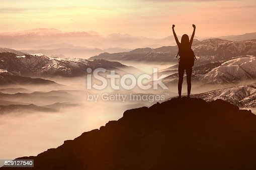 istock Woman Silhouette at sunset  on hill 529127540