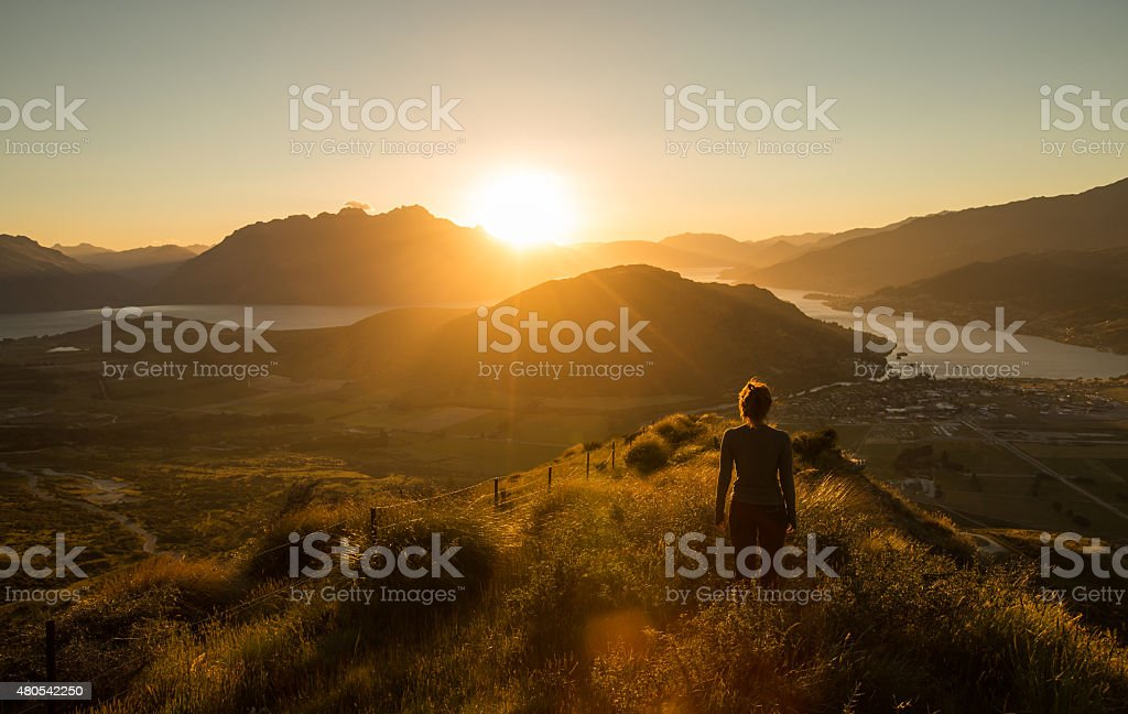 Woman silhouette at sunset on the mountain stock photo