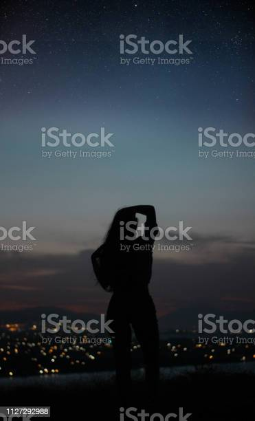 Photo of woman silhouette back gazing the stars with city on the background