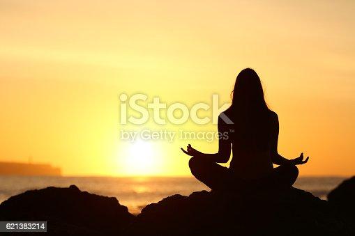 istock Woman silhouette doing yoga at sunrise 621383214