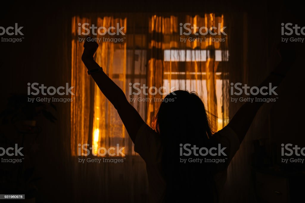 woman silhouette in front of window. sunrise in window. Wake up in morning stock photo