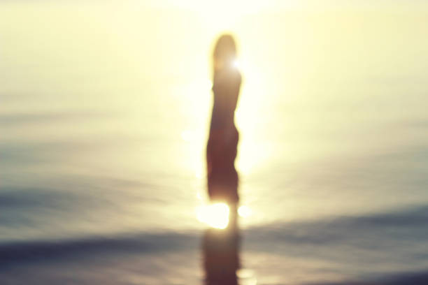 Woman silhouette on the sunset background. stock photo