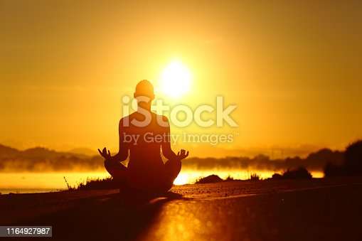 Woman silhouette practicing yoga exercise at sunrise