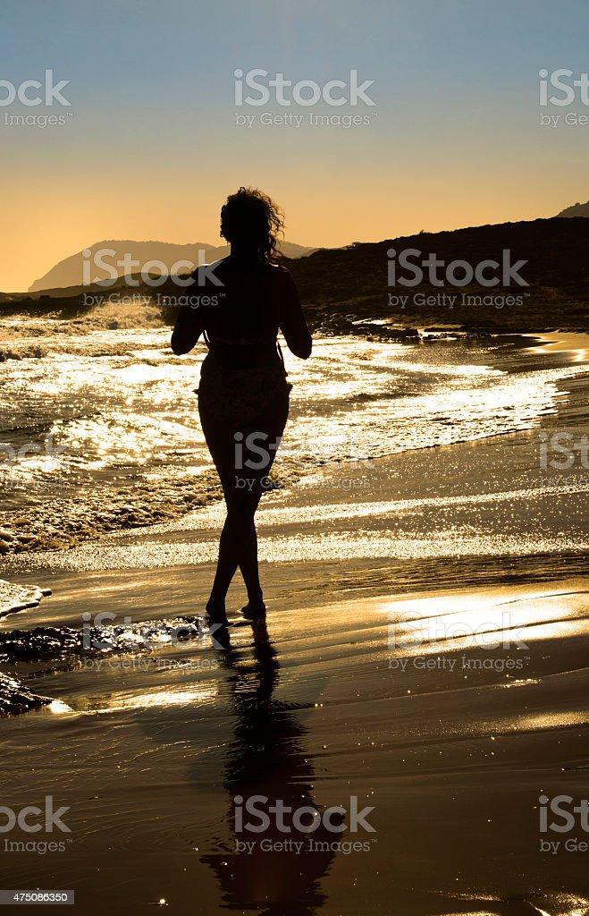 Woman silhouette walking on an empty beach stock photo