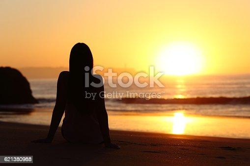 istock Woman silhouette watching sun at sunset 621380988