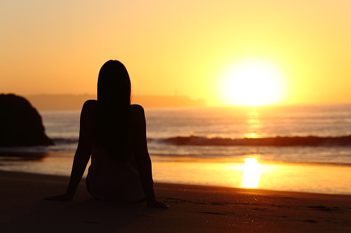 Woman silhouette watching sun at sunset