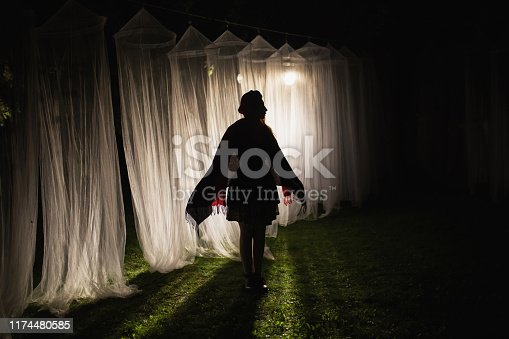 Woman silhouette. White long canopies are illuminated by the light of the lantern on a dark night. Conceptual photography. Mysterious silhouette on a dark background. Anonymous person