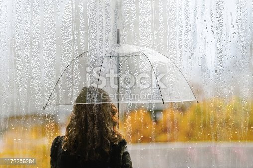 A woman silhouette with transparent umbrella through wet window with drops of rain. Autumn