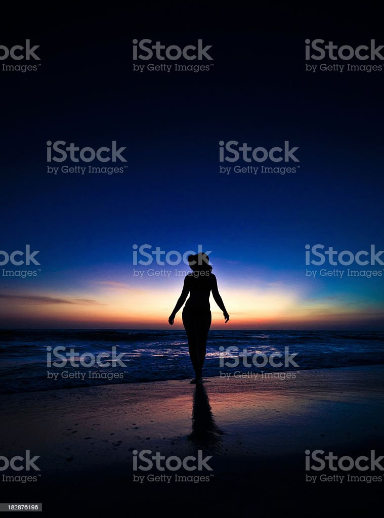 woman silhouetted on the beach stock photo