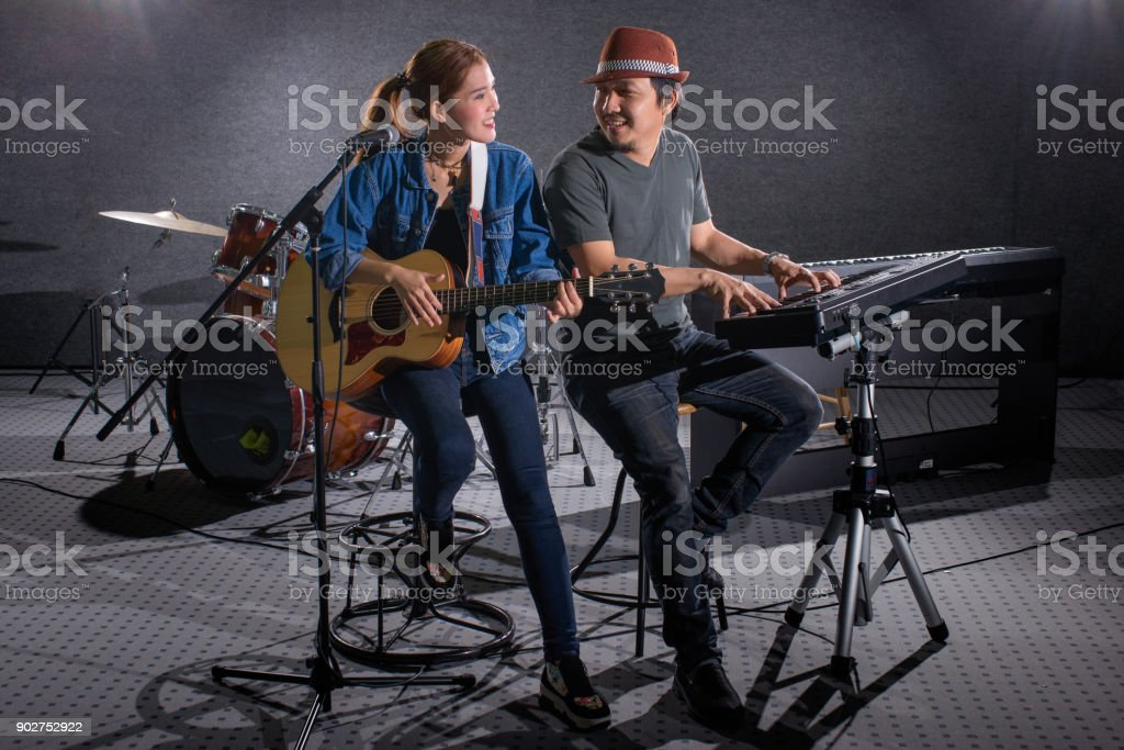 woman singer while playing Guitar  and man playing keyboard stock photo