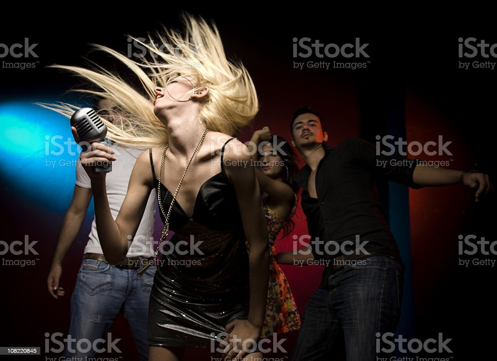 Woman Singing and Dancing With Crowd Behind Her royalty-free stock photo