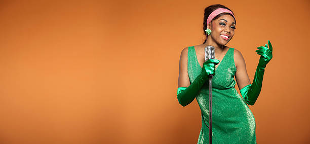 Woman singing in green vintage-style clothing and microphone stock photo