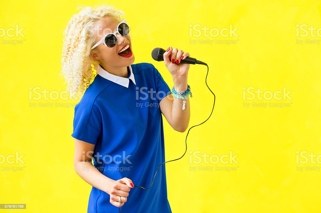 Woman singing in microphone stock photo