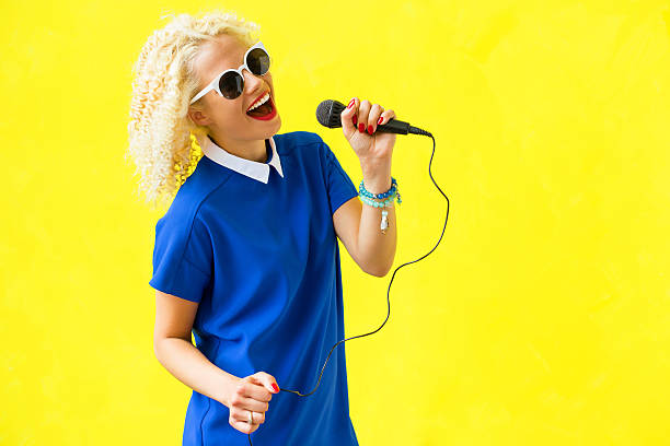 女性シンガーのマイクロフォン用マイクロフォンホルダ - ポップミュージシャン ストックフォトと画像