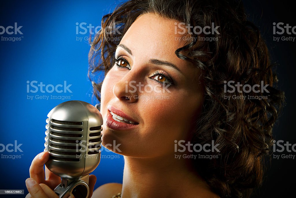 Woman singing into microphone against blue background stock photo