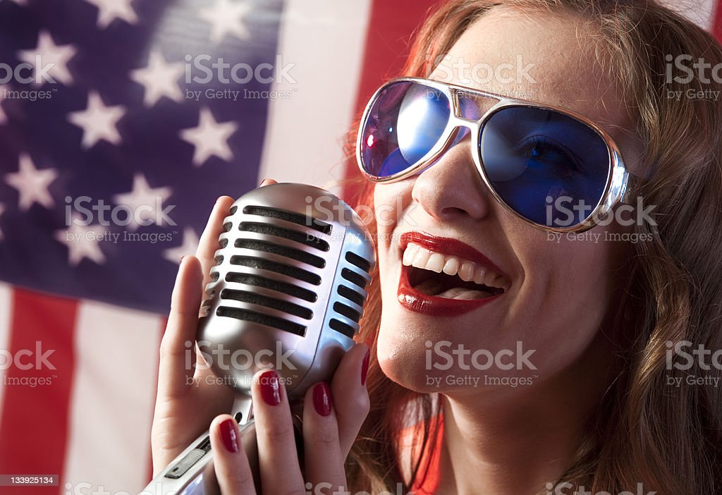 Woman Singing into Microphone stock photo