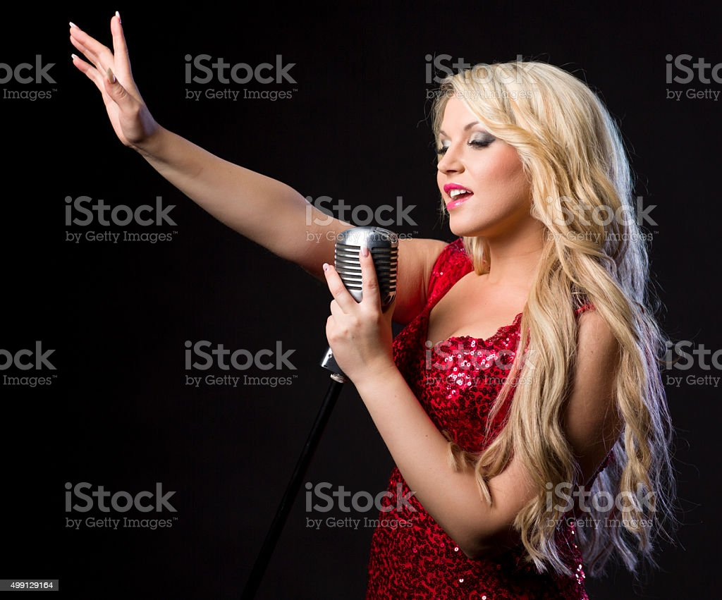 Woman singing into the microphone stock photo