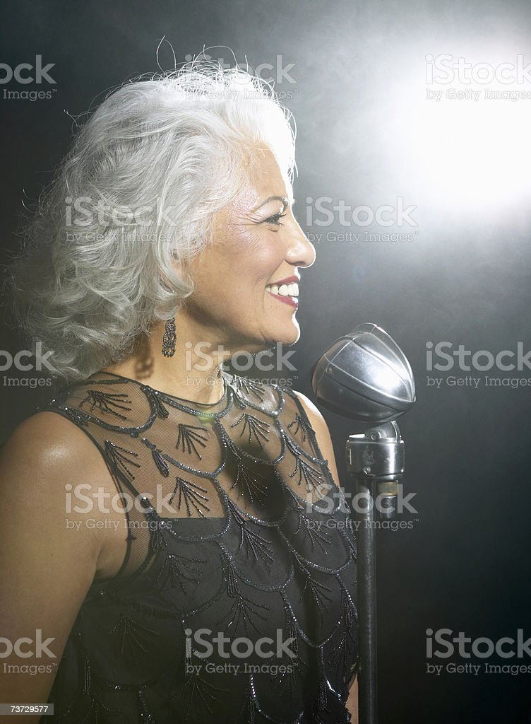 Woman singing into vintage microphone, profile royalty-free stock photo
