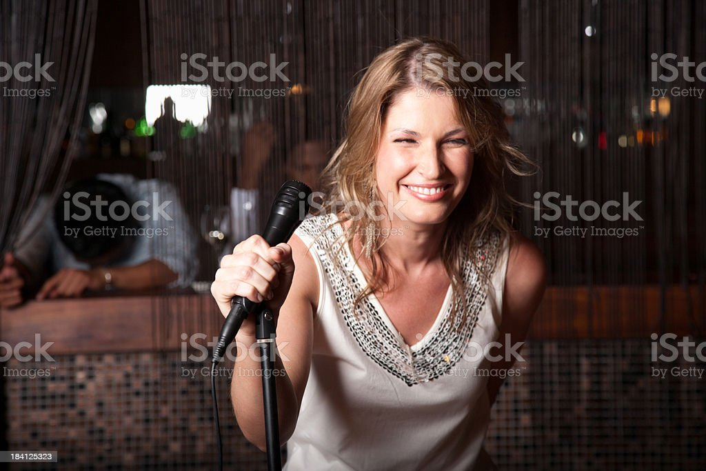 Woman singing out at a club stock photo