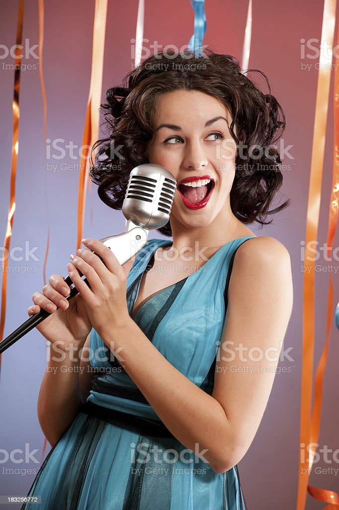 Young woman singing into microphone
