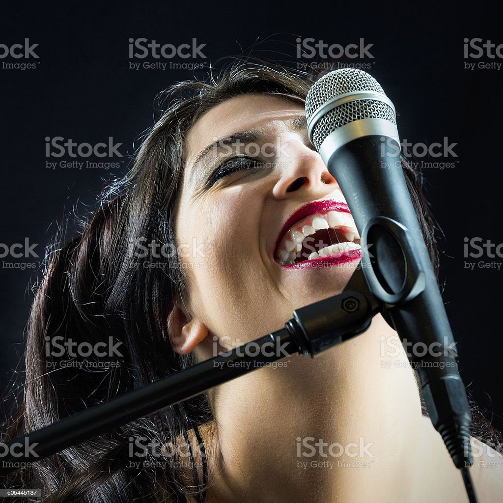 Woman Singing With Microphone stock photo