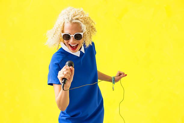 女性は、歌ったり、マイクロフォン - ポップミュージシャン ストックフォトと画像