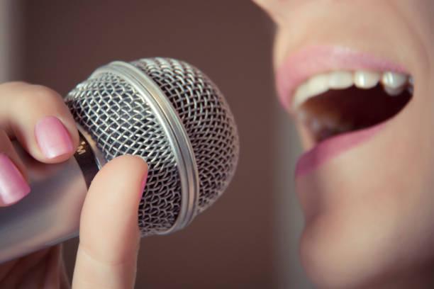 eine frau singt in ein mikrofon in einem tonstudio der mund nahaufnahme. - menschlicher mund stock-fotos und bilder