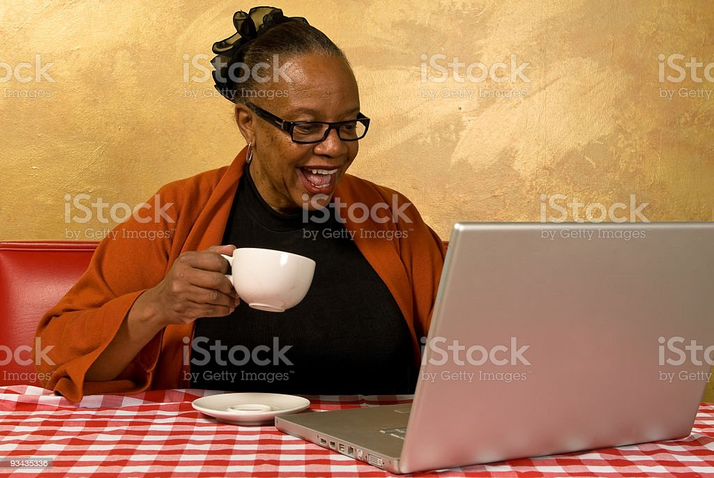 A woman sipping a cup of coffee in an Internet cafe stock photo