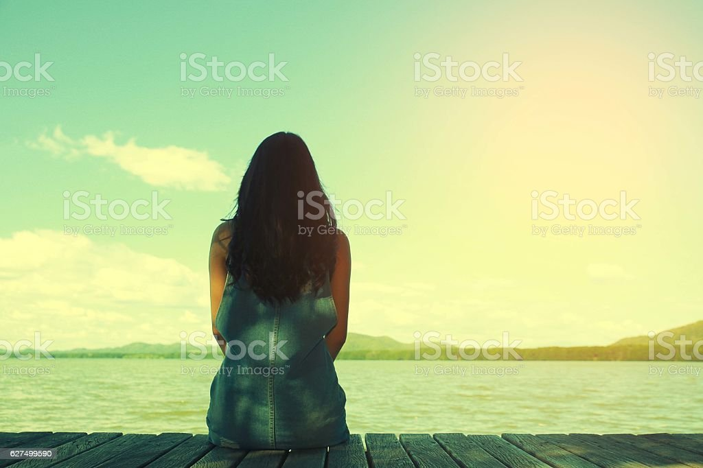 woman sit alone at the edge of bridge - Photo