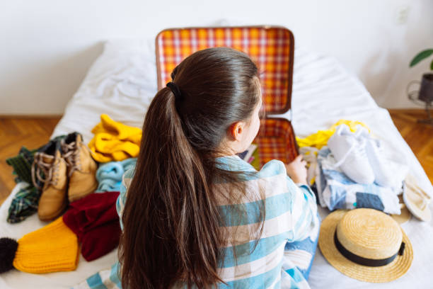 woman sit on bed with suitcase and clothes around. travel concept. decide warm or cold country to go. stock photo
