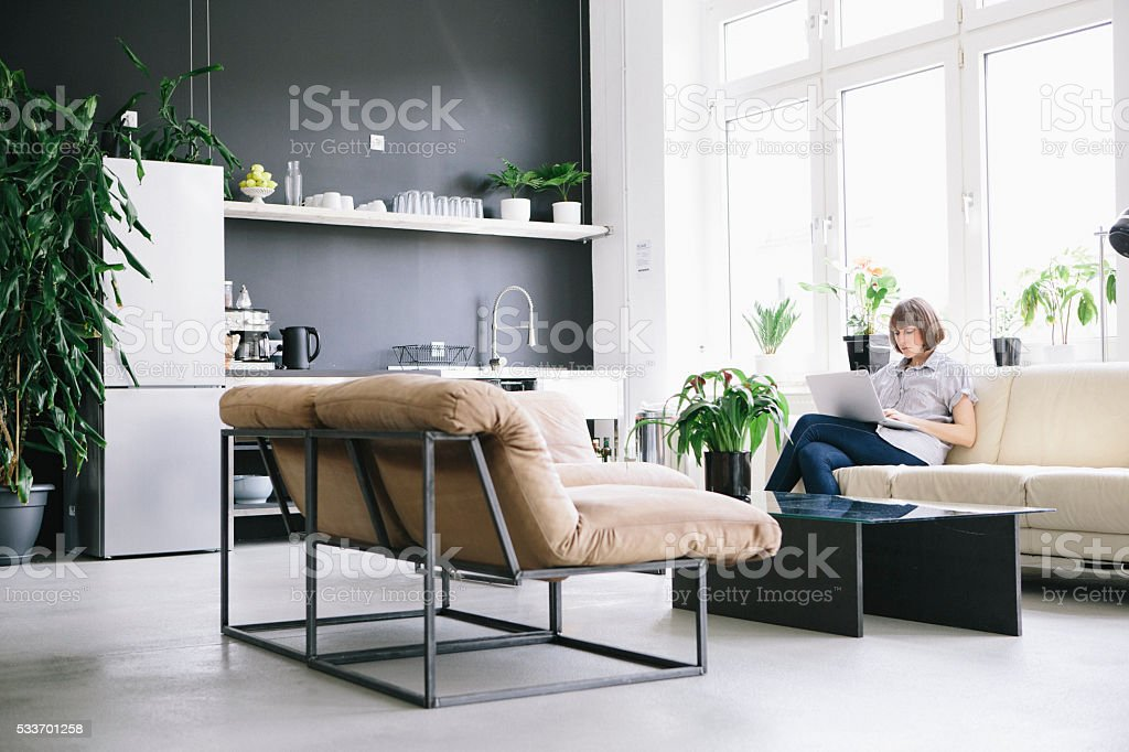 woman sit on couch in loft and work at laptop