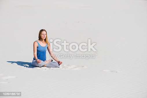 istock Woman sit on sand in yoga lotus position 1039188732