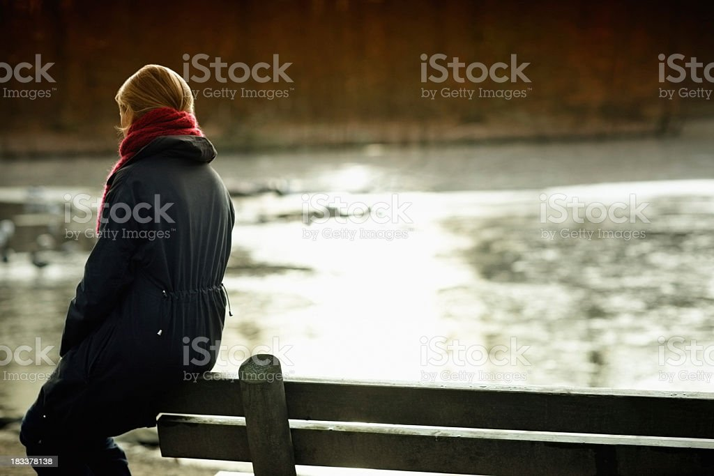 woman sits alone on a bench across the river royalty-free stock photo