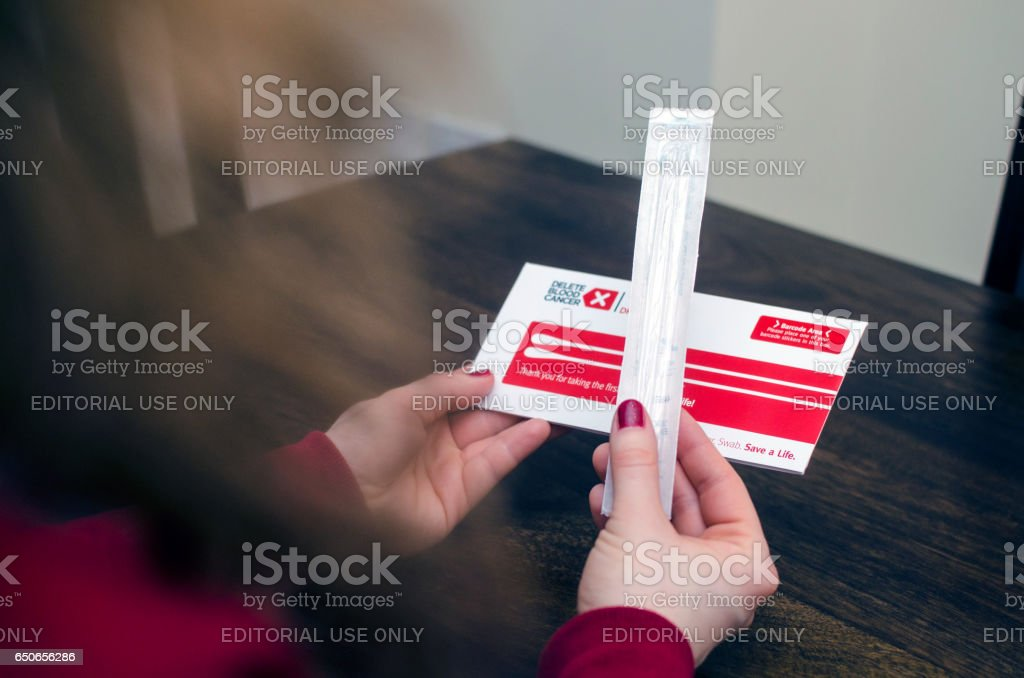 Woman sits at a table and is holding a Delete blood cancer campagne swab stock photo