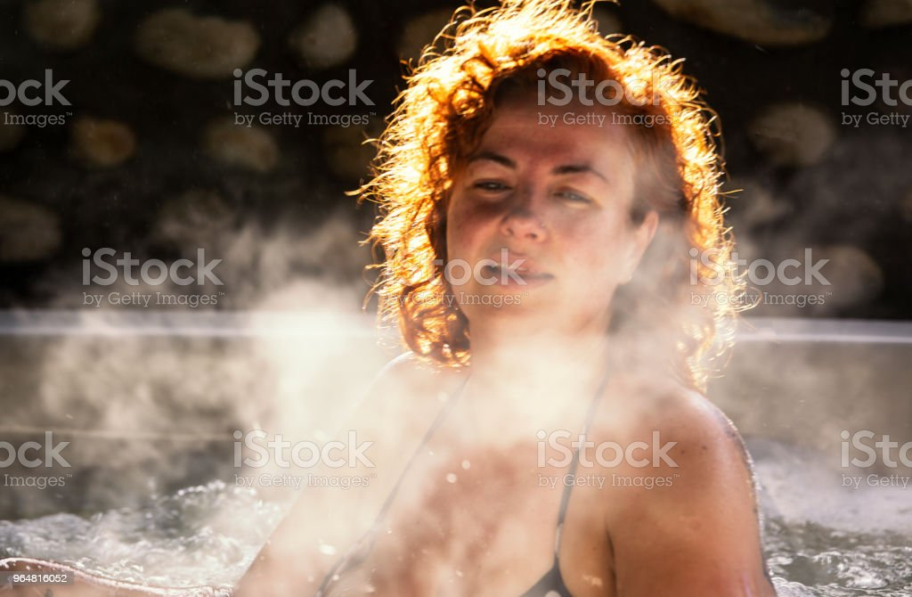 Woman sits in a steaming hot tub royalty-free stock photo