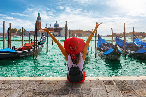 Woman sits in front of the traditional gondolas of St. Mark`s Square in Venice, Italy