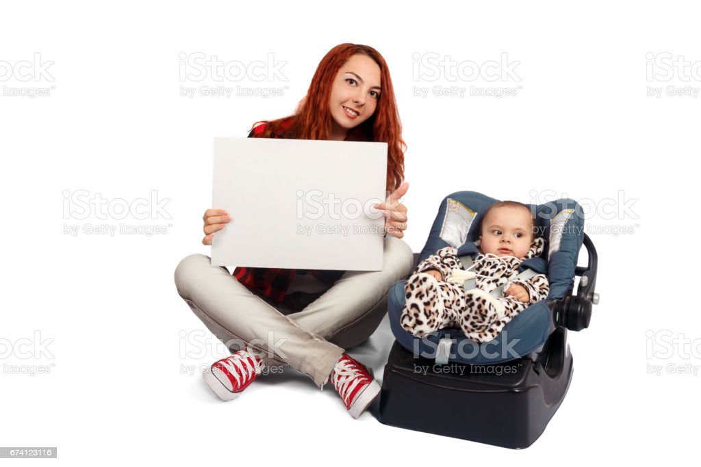 Woman sits near her newborn daughter in a car safety seat, isolated white background. royalty-free stock photo