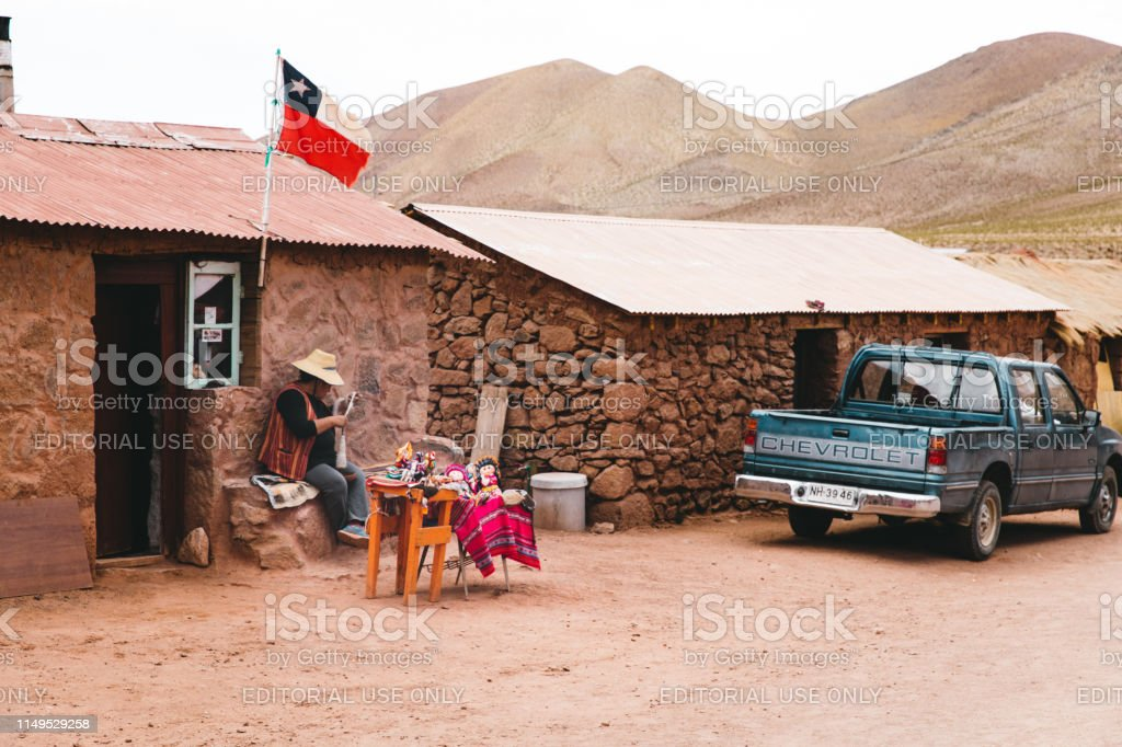 Woman sits near her home making souvenirs and seeing it to tourists...