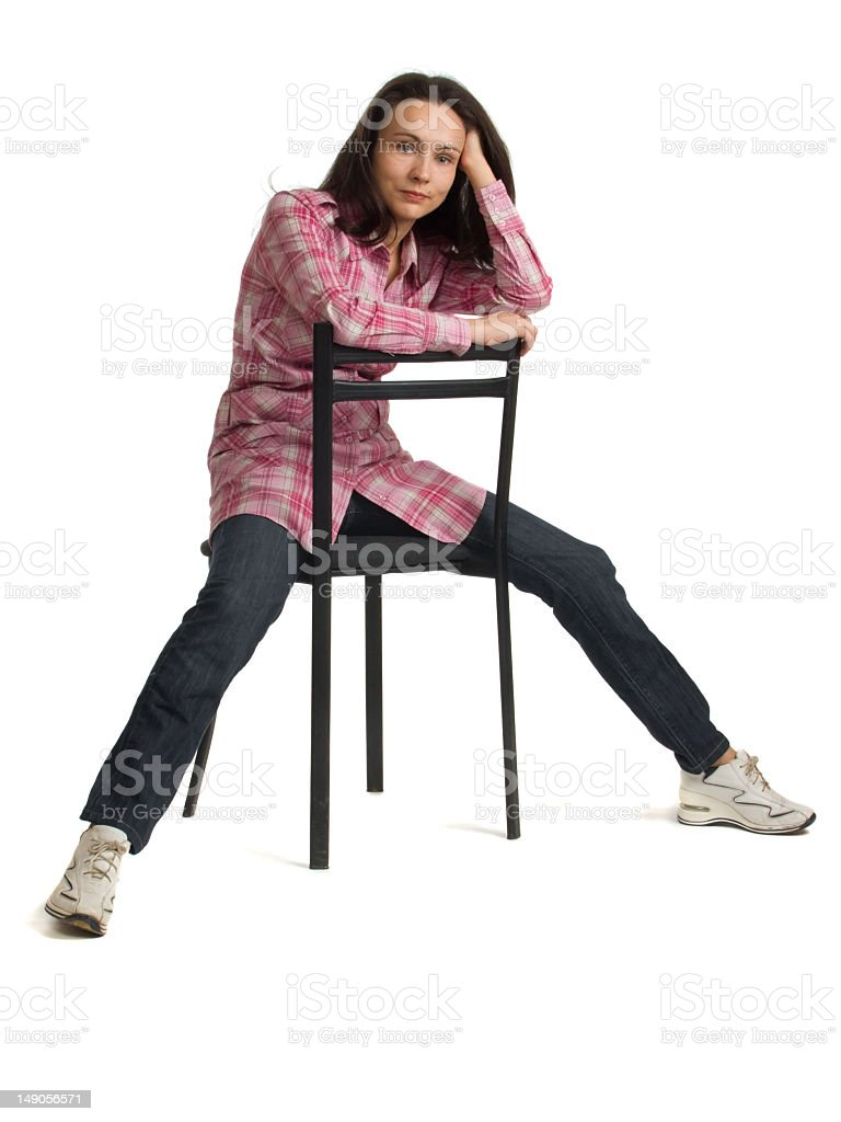 Woman sits on a chair back to front. stock photo