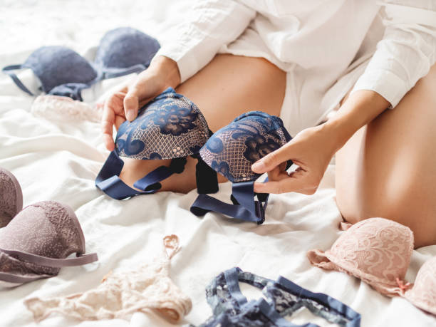 Woman sits on an unmade bed and chooses underwear. Various bras in front of female. Pleasant morning routine. Bedroom lit with sunlight in cozy home. stock photo