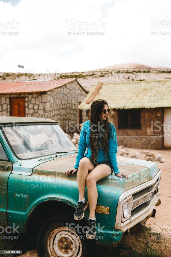 Woman in sunglasses resting after road trip through Atacama region in...