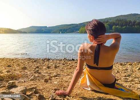 istock A woman sits on the beach and looks at the water 1026843494