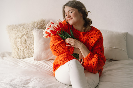 Woman sits on the bed at home and rejoice at tulips